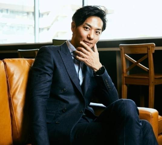ソファに座るバチェラーシーズン3に出演した友永真也